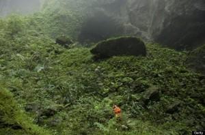 A Hang Son Doong explorer navigates an plant-covered cavescape.