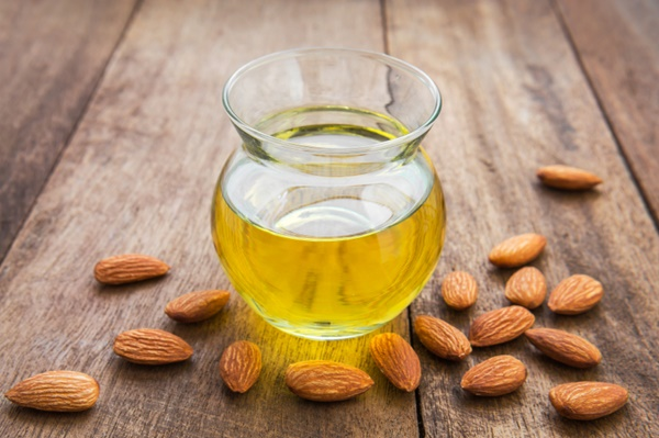 Almond oil in glass bottle and almonds